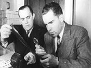 Senators Joseph McCarthy and Richard Nixon scan microfilm for clues of Soviet spies in America, 1950s